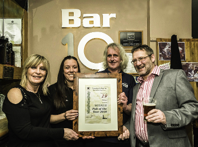Landlord Lee Rawlings with Bar 19 staff, Rob Wheatley (right) and the Pub of the Year 2018 Award